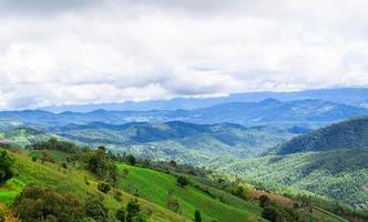 paisaje de hermosas montañas con prados verdes y cielo azul por la mañana. foto