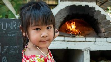 A little girl makes hand made pizza and stands smiling in front of a wooden brick pizza oven in an outdoors courtyard at a restaurant. photo