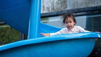 Asian little child girl having fun to playing slide at playground in summer time. Playing is learning in childhood. photo