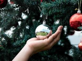 Close up of hand holding on Christmas baubles, balls on Christmas tree branch. Happy new year. Festive background. Merry christmas. photo