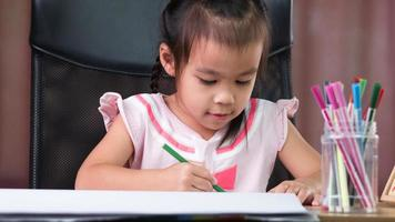 A cute little girl is drawing a rainbow on paper with colored pencils at the table at home. photo
