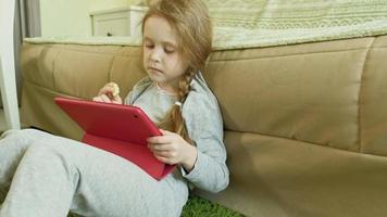 menina sentada no chão usando um tablet de computador video
