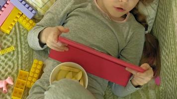 little girl uses a computer tablet in the interior video