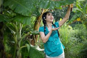 Portrait of a young Asia woman with black hair holding a banana leaf in the raining at the green garden background photo