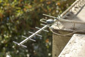 A TV antenna installed on an old balcony photo