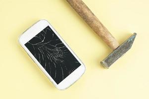Un teléfono celular con pantalla rota y un martillo sobre fondo marrón foto