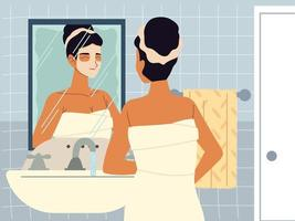 beautiful woman moisturizing face with cream or cleansing lotion in front of mirror, skincare vector