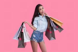 Happy Asian woman with shopping bags in a pink background. E-commerce and shopping online concept. photo