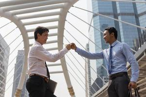 Two businessmen giving bump for business success and completing a deal. Teamwork in work for success. photo