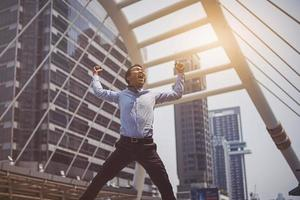 Happy Asian businessman jumping in the city after success business deal photo