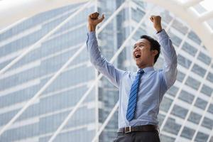 Businessman holds up hand after successful business and standing outdoors with office building in the background photo