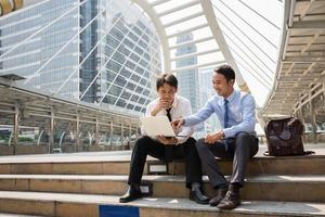 Two businessmen are working with smart phone and notebook for business concept. photo