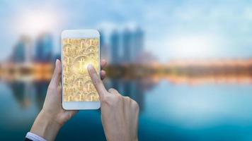 Hand touching bitcoin in smart phone photo