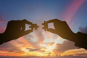 Silhouette of businesspeople hands connecting puzzle. Business teamwork concept. photo