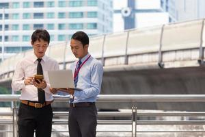 Two businessmen are working on sidewalk with smart phone and notebook for business concept. photo