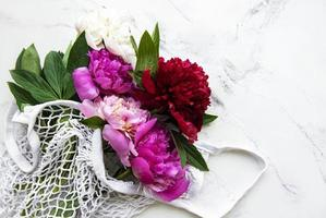 Pink peony flowers in string bag photo