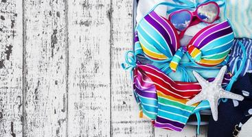 Colorful bikini and clothes in luggage on the wooden background photo