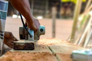 Una mano de carpintero sosteniendo un avión eléctrico trabajando en un piso de madera, nuevas ideas para la construcción de viviendas e industria de productos de madera foto