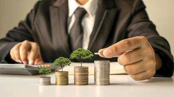 un empresario sosteniendo una moneda con un árbol que crece y un árbol que crece sobre una pila de dinero. la idea de maximizar el beneficio de la inversión empresarial. foto