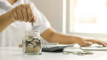 Los hombres de negocios están poniendo monedas en un frasco de ahorros, incluido un centavo creciente para ideas comerciales, financieras y contables. foto