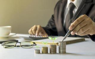 empresario sosteniendo una pluma y un árbol que crece en una moneda, planeando ideas para invertir y hacer crecer el dinero. foto