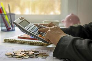 primer plano de mujeres que utilizan calculadoras y toma de notas, informes contables, ideas de cálculo de costos y ahorro de dinero. foto