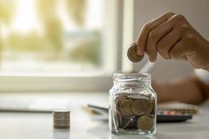 primer plano de mujer joven poniendo monedas en una botella, ahorrar dinero, concepto de ahorro de dinero para la contabilidad financiera. foto