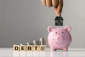 Concept of debt and financial goals.Coin on stacked wooden blocks labeled debt and hands holding house model in pink pig savings. photo