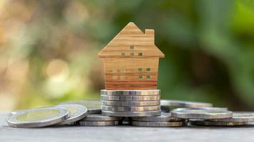Wooden house model on coin pile and blurred green nature background, real estate investment and home loan concept. photo
