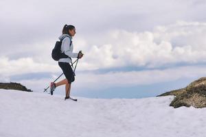 Chica apasionada de los deportes al aire libre durante la caminata sobre la nieve. foto