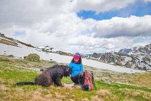 A woman from food to her dog during a walk in the mountains photo