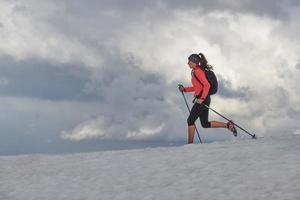 chica skyrunning practica en la nieve en las montañas foto