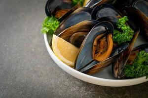 Mussels with herbs in a bowl with lemon photo