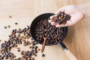 Roasted coffee beans in hand photo