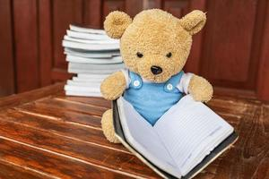 el oso de peluche está sentado leyendo un libro leyendo conceptos foto