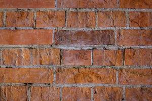 Red brick wall with light seams and uneven surface photo
