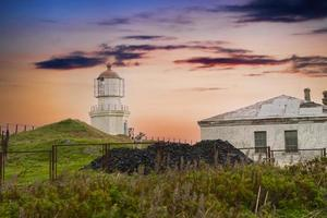 Landscape with an old lighthouse on the background of the sunset photo