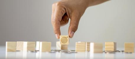 Business man hand close up select goal and target icon on wooden block target concept business success. photo