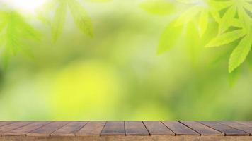 Wooden table background with cannabis leaf backdrop and blurred green nature backdrop for product display. photo