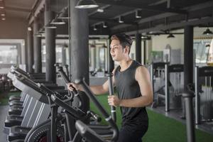 Handsome man running on a treadmill in a gym photo