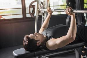 Athletic man pumping up muscles on bench press photo