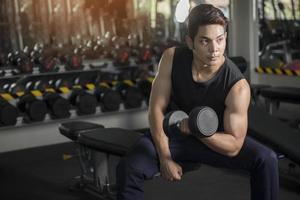 Hombre con equipo de entrenamiento con pesas en el club de gimnasia deportiva foto