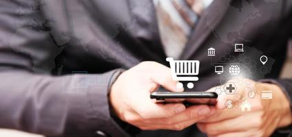 Businessman using smartphone with shopping cart icon photo