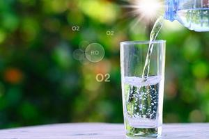 Water from bouttle pouring into glass on wooden table and mineral water health care concept, space for text photo