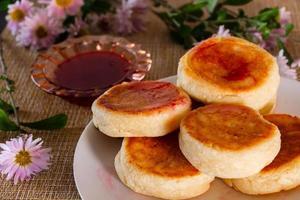 desayuno casero: panqueques de requesón en un plato con mermelada y crema agria. foto