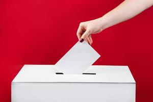 Woman puts a ballot paper in voting box on red background. Elections in the United States. photo