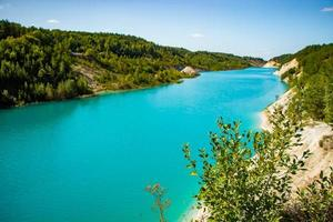 Beautiful mountain landscape - a lake with unusual turquoise water in the crater. Chalk quarry in Belarus. photo