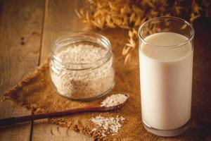 Glass of oat milk on a wooden background photo