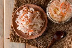 Homemade sauerkraut on a linen background. Rustic style, canned vegetables on a light wooden background. Eco food, the trend of healthy eating. photo