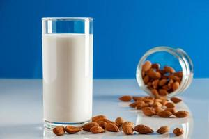 Gluten free almond drink on a blue background. Super Food - A glass of almond milk for a healthy diet. photo